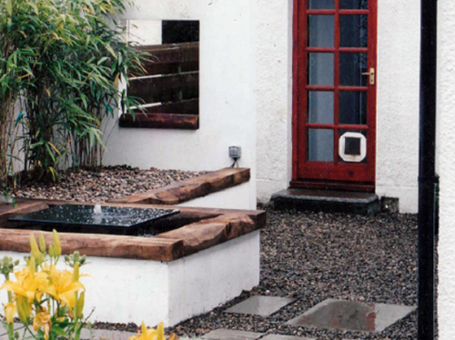 Black marble water feature with railway sleeper coping.
